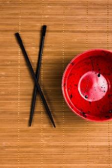 Gros plan d'un bol rouge vide avec des taches de sauce soja et des baguettes noires sur fond de napperon marron