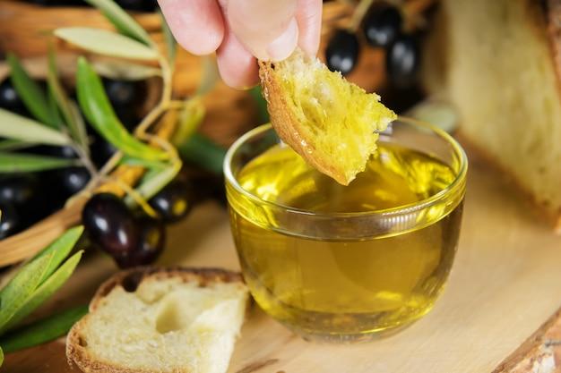 Gros plan d'un bol en verre plein d'huile d'olive avec du pain et des brunchs aux olives. graisses saines