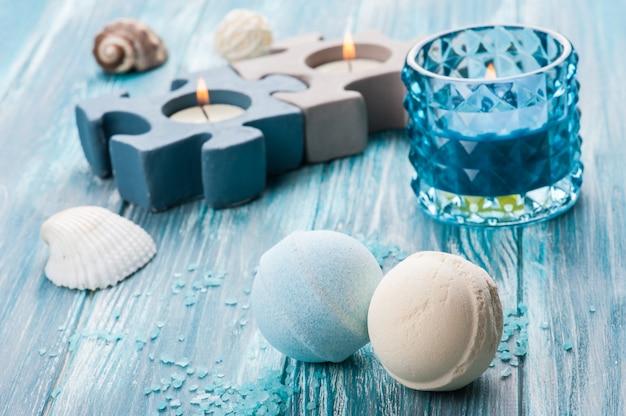 Gros plan de bombes de bain avec une bougie allumée bleue