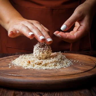 Gros plan des bonbons à la main des bonbons à la main à partir de noix, de fruits secs et de miel