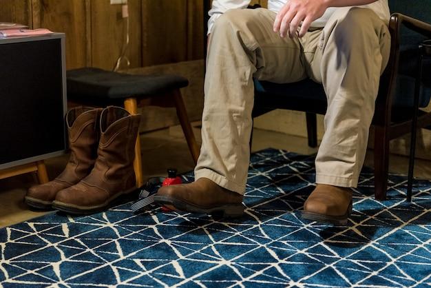 Gros plan sur des bottes et un homme assis sur une chaise
