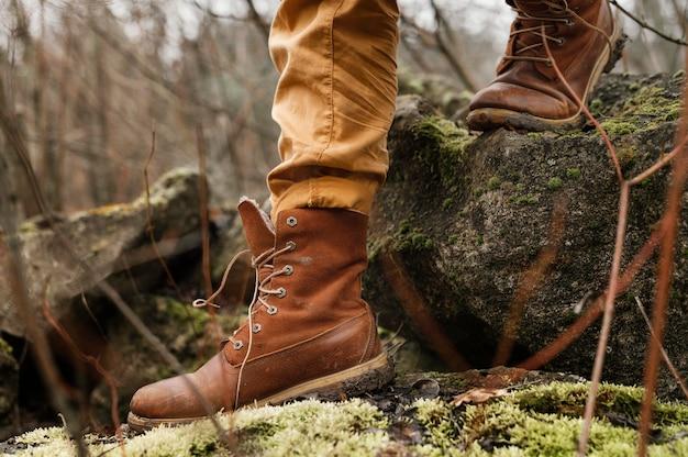 Gros plan des bottes marchant dans la forêt