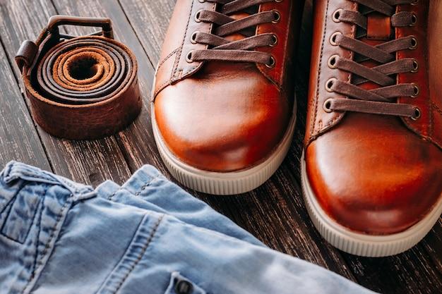 Gros plan des bottes pour hommes en cuir marron et blue jeans sur fond en bois foncé