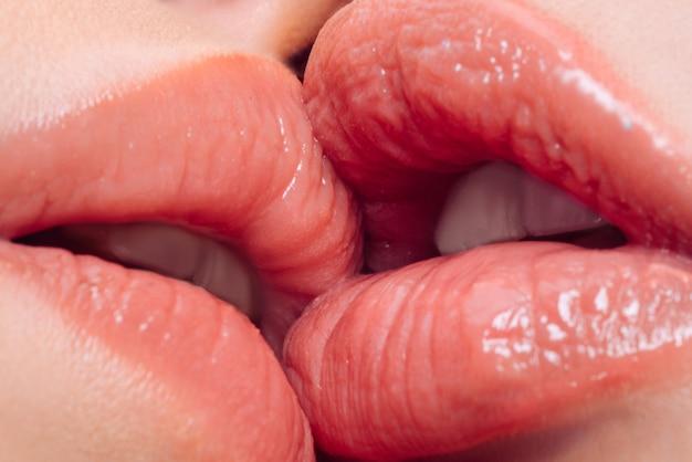 Gros plan de la bouche des femmes s'embrassant et se léchant les lèvres.