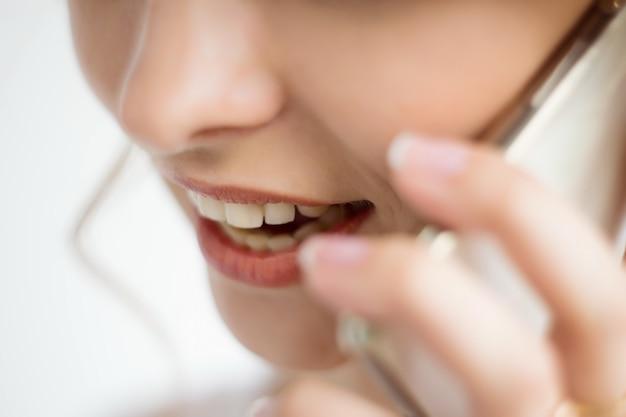 Gros plan sur la bouche et les lèvres d'une femme parlant sur un smartphone sur fond blanc. de belles dents blanches. service client.