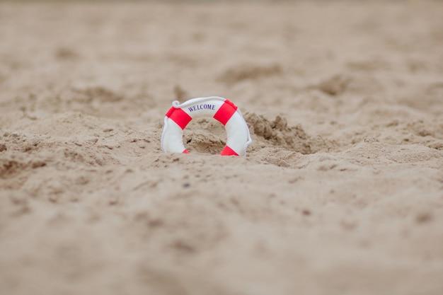 Gros plan d'une bouée de sauvetage miniature creuser dans le sable à la plage