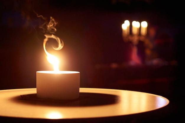 Un gros plan d'une bougie allumée sur une table dans le noir