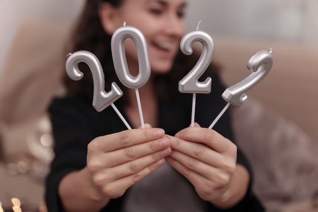 Gros plan de bougies sous forme de nombres 2022 dans des mains féminines.