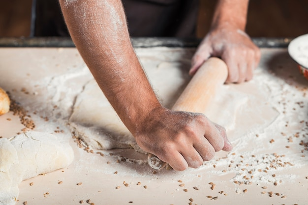 Gros plan, de, boulanger, main, aplatissement, pâte, sur, comptoir cuisine