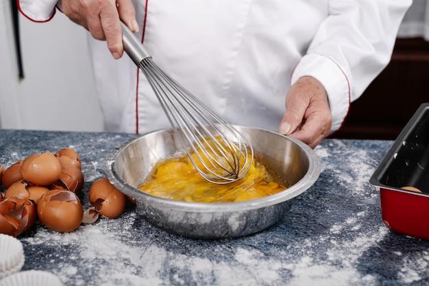 Gros plan d'un boulanger mélanger les œufs avec un mixeur plongeant