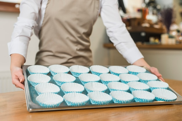 Gros plan d'une boulangère tenant un plateau en acier inoxydable avec des moules en silicone pour cupcakes disposés