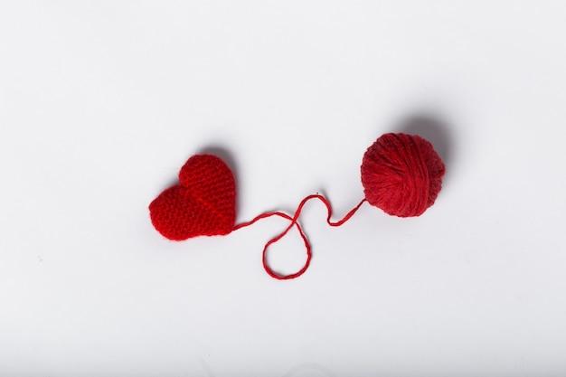 Gros plan d'une boule de laine et forme de coeur sur fond blanc. fil de laine en forme de coeur. love crochet.