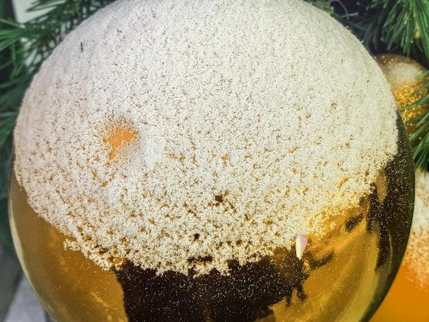 Gros plan sur une boule de noël brillante dorée recouverte de neige, le concept d'une décoration festive et d'un arrière-plan.