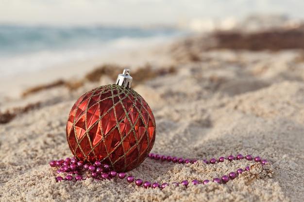 Gros plan d'une boule de noël rouge sur la plage au lever du soleil, vacances