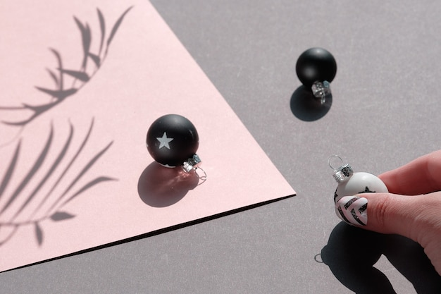 Gros plan sur des boules de noël noir et blanc sur papier rose et gris.