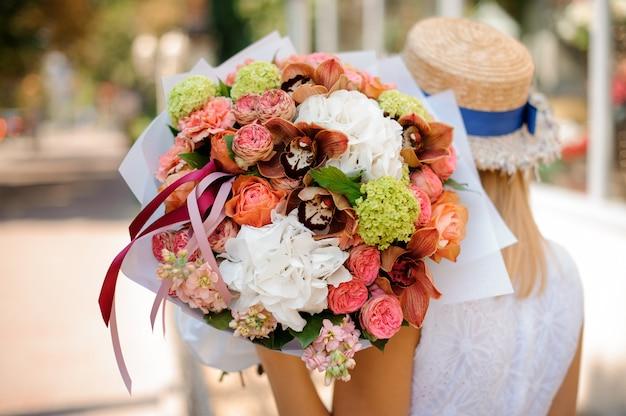 Gros plan d'un bouquet coloré dans les mains d'une fille sans visage