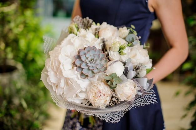 Gros plan de bouquet. la combinaison de pivoines, de roses et de plantes succulentes
