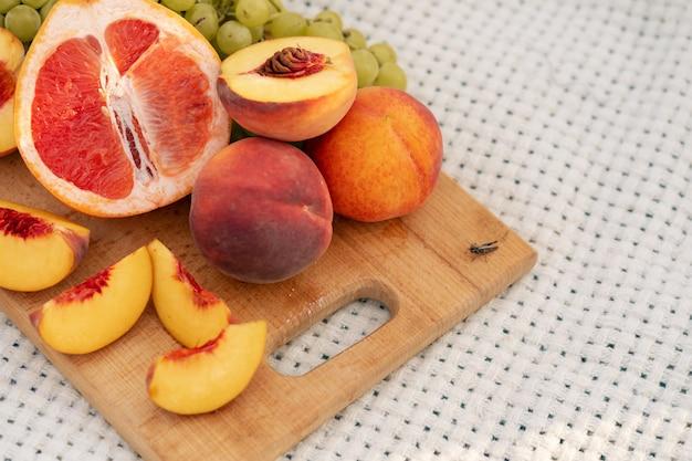 Gros plan d'un bouquet de fruits frais sur une planche à découper. pique-nique à l'extérieur