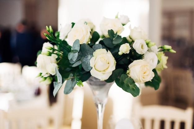 Gros plan d'un bouquet de roses blanches dans un vase transparent lors d'une réception de mariage