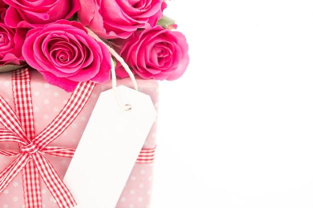 Gros plan d'un bouquet de roses roses à côté d'un cadeau rose avec une carte vierge sur un fond blanc