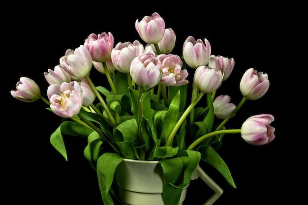 Gros plan d'un bouquet de tulipes roses dans un vase art déco