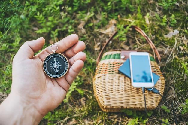 Gros plan, boussole dans la main d'un gars. en arrière-plan powerbank avec un smartphone sur un panier dans la forêt.