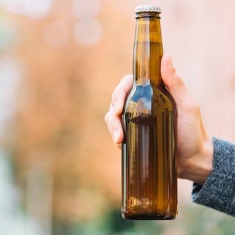 Gros plan d'une bouteille de bière à la main