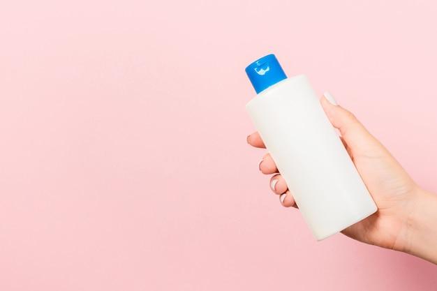 Gros plan d'une bouteille de cosmétiques dans une main féminine sur fond rose