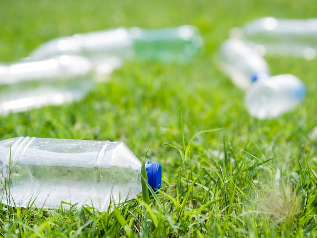 Gros plan d'une bouteille d'eau en plastique sur l'herbe au parc