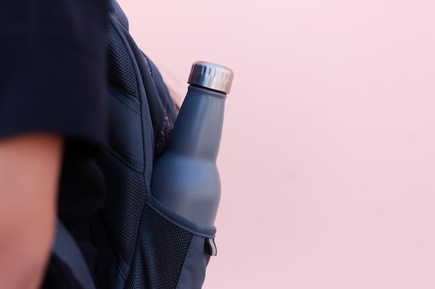 Gros plan d'une bouteille d'eau thermo éco en acier réutilisable de couleur bleue dans la poche du sac à dos. fond rose pastel. concept de temps scolaire. soyez sans plastique.