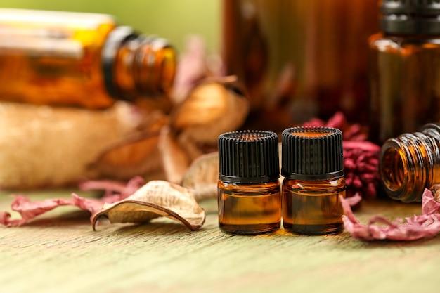 Gros plan sur des bouteilles d'huile essentielle d'ambre entourées de fleurs séchées avec un arrière-plan flou