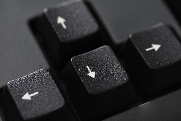 Gros plan d'un bouton fléché noir du clavier
