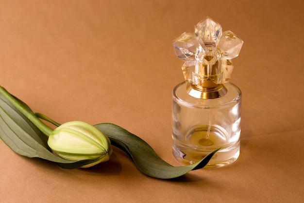 Gros plan sur un bouton floral de lys fermé et une bouteille de parfum