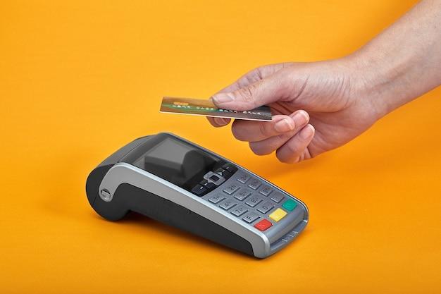 Gros plan des boutons de la machine de paiement avec main humaine tenant une carte en plastique à proximité sur une surface jaune.