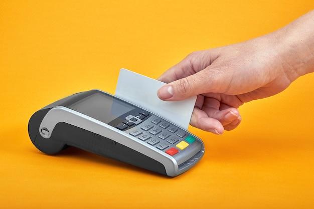 Gros plan des boutons de la machine de paiement avec main humaine tenant une carte en plastique à proximité sur le tableau jaune