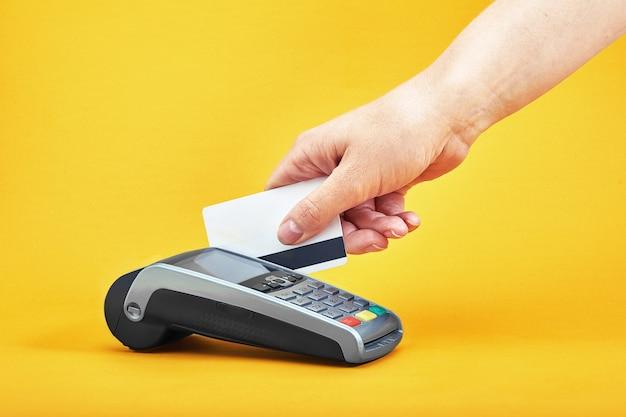 Gros plan des boutons de la machine de paiement avec main humaine tenant une carte en plastique