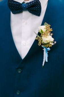 Un gros plan des boutons de roses blancs du marié sur une veste bleue et un élégant nœud papillon bleu