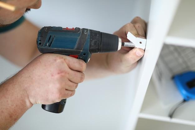 Gros plan d'un bricoleur perçant des détails métalliques pour un nouveau travailleur professionnel de placard blanc utilisant