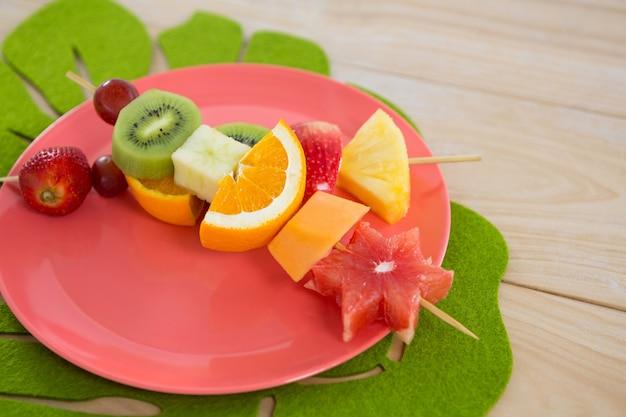 Gros plan, de, brochettes de fruits, dans, assiette, sur, table bois