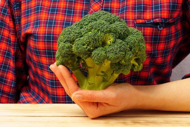 Gros plan de brocoli dans une main féminine dans le contexte d'une chemise à carreaux.