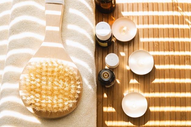 Gros plan d'une brosse de bain avec des huiles essentielles et des bougies. concept spa.