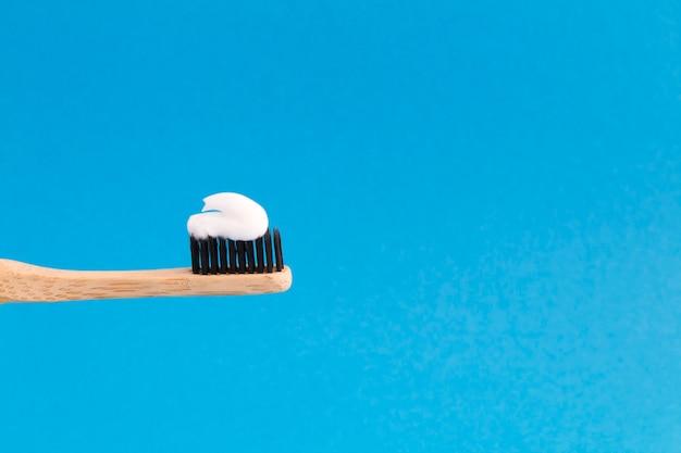 Gros plan sur la brosse à dents en bambou avec de la pâte blanche sur le fond bleu