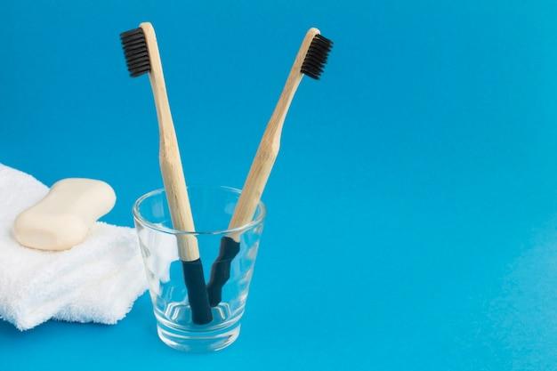 Gros plan sur des brosses à dents en bambou sur le verre, des serviettes blanches et du savon sur le fond bleu