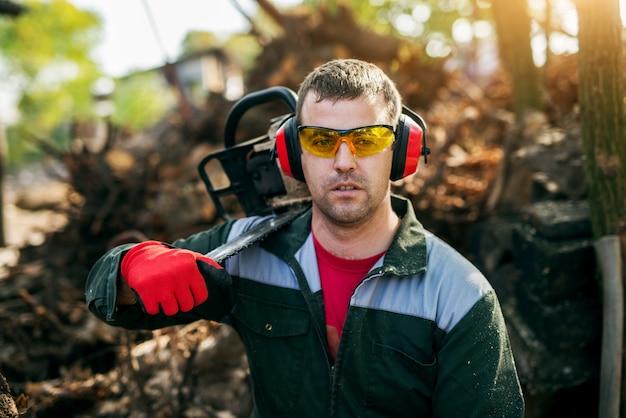 Gros plan d'un bûcheron professionnel avec des lunettes et une protection auditive tenant une tronçonneuse sur l'épaule tout en faisant une pause.