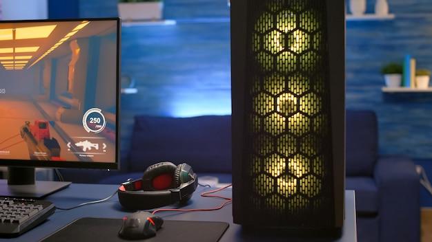 Gros plan sur le bureau du système rvb, un joueur professionnel jouant à un jeu vidéo de tir à la première personne lors d'une compétition en ligne. le studio de streaming est équipé d'une configuration professionnelle avec un pc puissant prêt pour le jeu en ligne