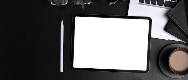 Gros plan sur un bureau sombre avec tablette numérique, stylet, ordinateur portable