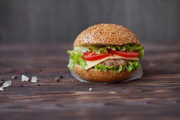 Gros plan de burgers de boeuf faits maison avec de la laitue et de la mayonnaise servis sur une petite planche de bois. fond sombre