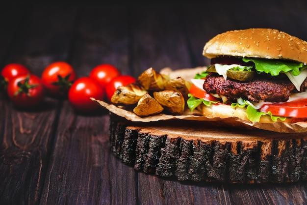 Gros plan de burgers de bœuf faits maison avec de la laitue et de la mayonnaise, servis sur une petite planche à découper en bois.