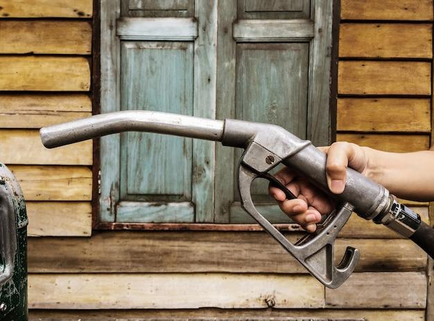 Gros plan de la buse de la pompe à essence à la station-service avec fond en bois.