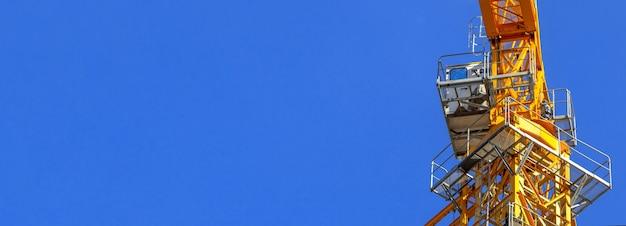 Gros plan de cabine de grue de construction jaune sur fond de ciel bleu, photo de l'espace de copie de bannière